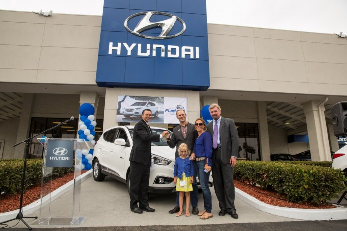 Timothy Bush and his family accepting the keys to the very first Hyundai Tucson Fuel Cell vehicle