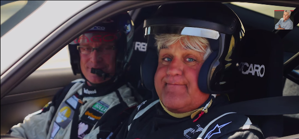Race car driver Kelly Collins (left) and comedian Jay Leno (right), who's helmet can barely contain his face test driving a Porsche 911