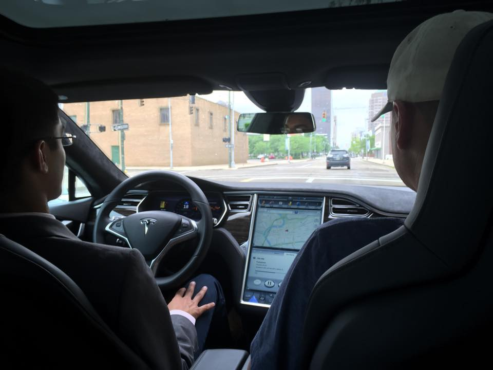 D'Souza puts his hands on his lap to demonstrate the Model S' autonomous technology