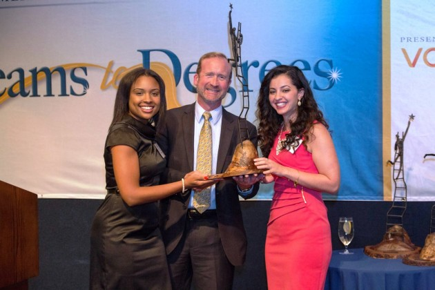 Morgan Grayned (left) and Zineb Bouzoubaa (right) present Greg Martin, executive director of GM Global Public Policy, with the Social Responsibility Award from Scholarship America
