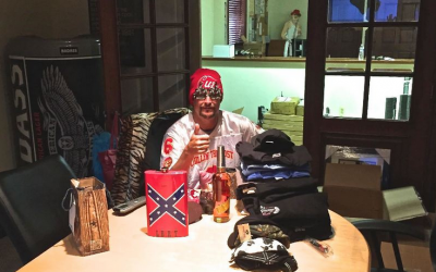Kid Rock poses with a Confederate flag flask given to him by fans