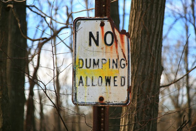 man defecates in police car - no dumping allowed sign