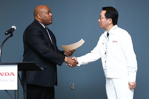 Honda Aero President Atsukuni Waragai accepts the PART 145 repair station certificate from Jeffrey Phipps, manager of the FAA's Flight Standards District Office in Greensboro.