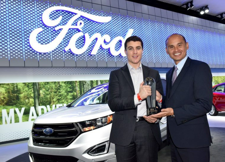 Jim Nguyen (right), TrueCar EVP, hands Ford's Omar Odeh (left) a trophy for the automaker's three wins in the inaugural TrueCar Pre-Owned Value Awards at NYIAS