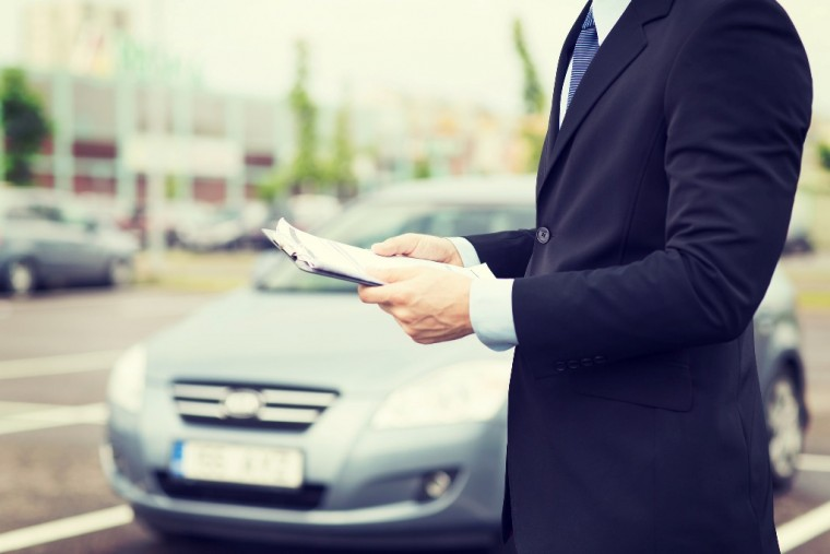 Businessman in suit with clipboard testing car