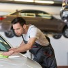 Man mechanic working on cleaning car in garage