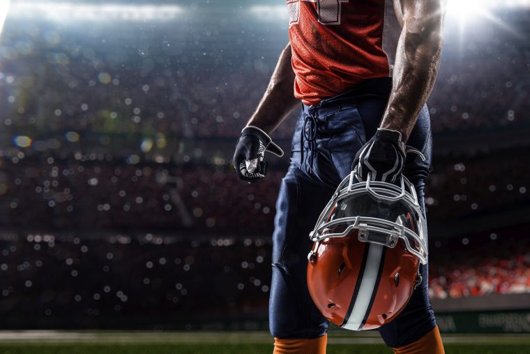 NFL Football player on field helmet orange jersey