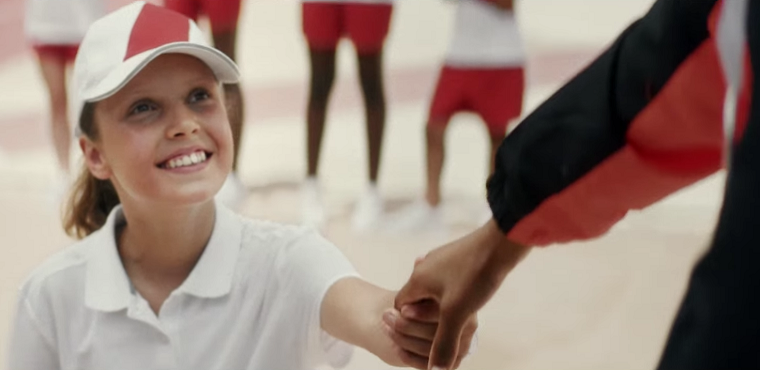 Girl holds medal winner's hand in Toyota ad