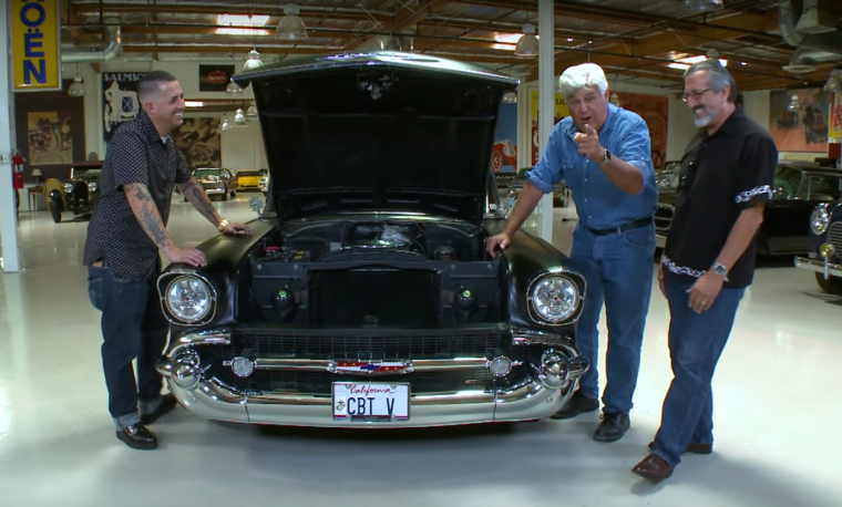 Jay Leno poses with a father and son team of US veterans and the 1957 Chevy 210 that they built together