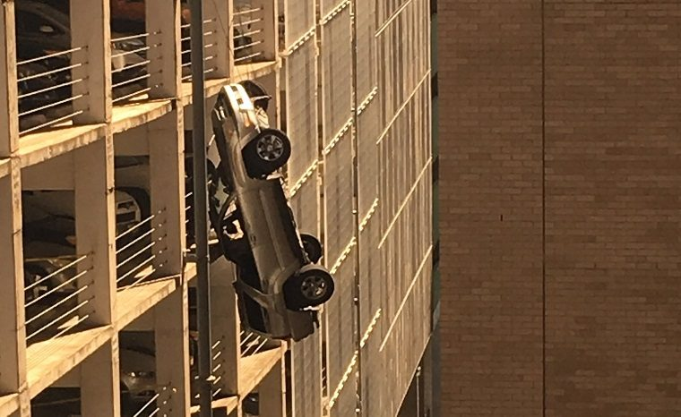 Toyota 4Runner dangles off parking garage