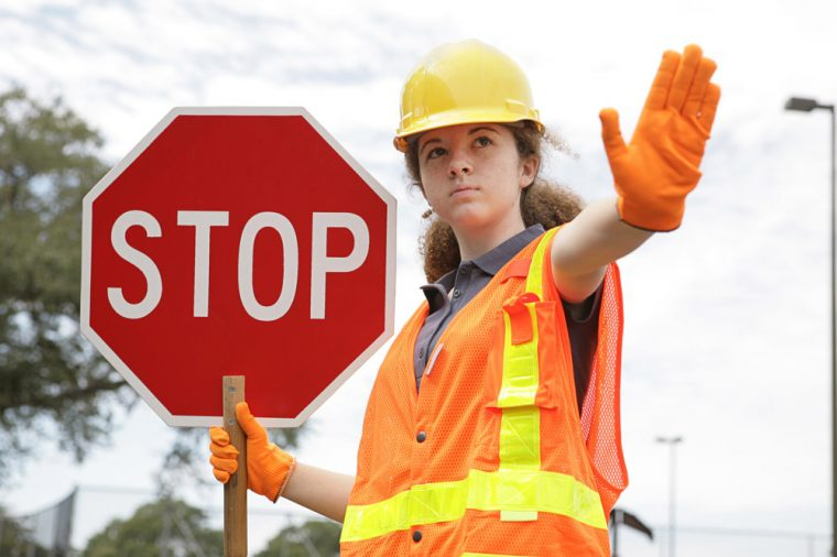 crosswalk girl red stop sign directing traffic