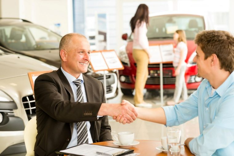 car sales man person shaking hands selling discount deal customer