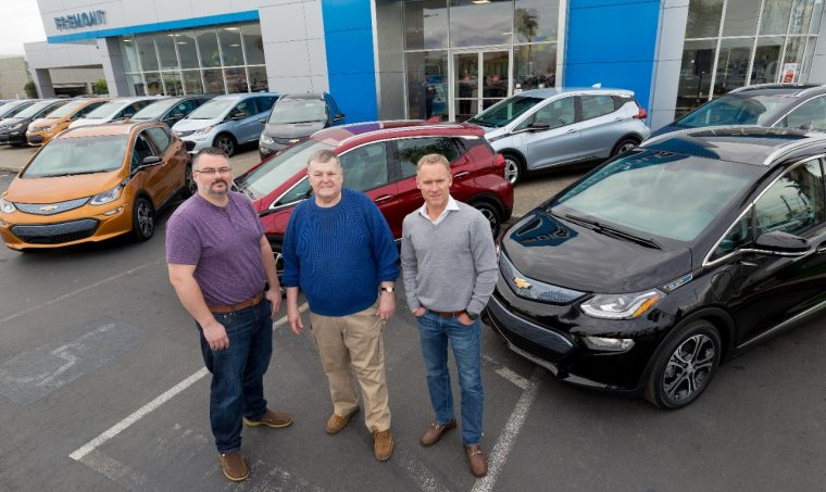 The first three 2017 Chevy Bolt EV customers in California pose with electric vehicle