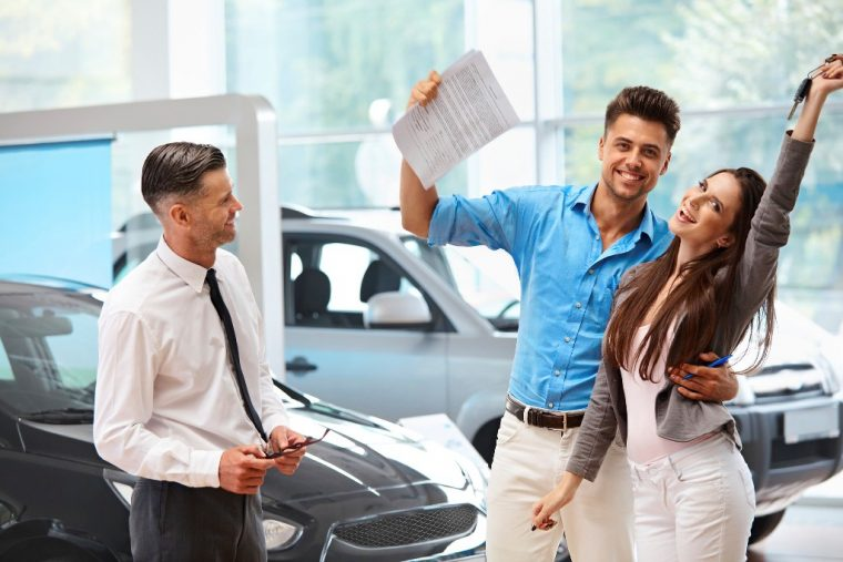 happy couple buying a used car from dealership low prices