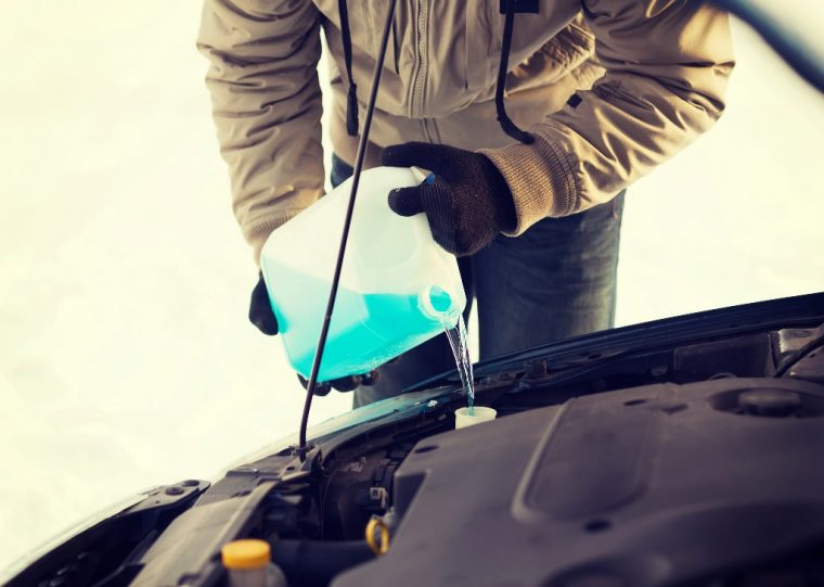 man pouring anti freeze engine gasoline freeze cold winter chill temperatures car