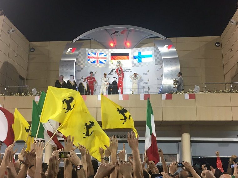 Vettel lifts the 1st place trophy next to Hamilton and Bottas