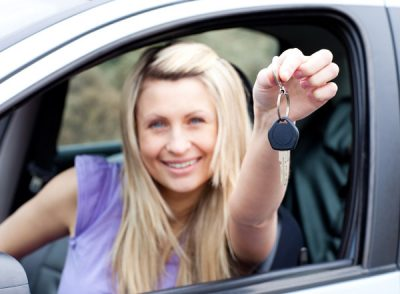 young driver holding out key
