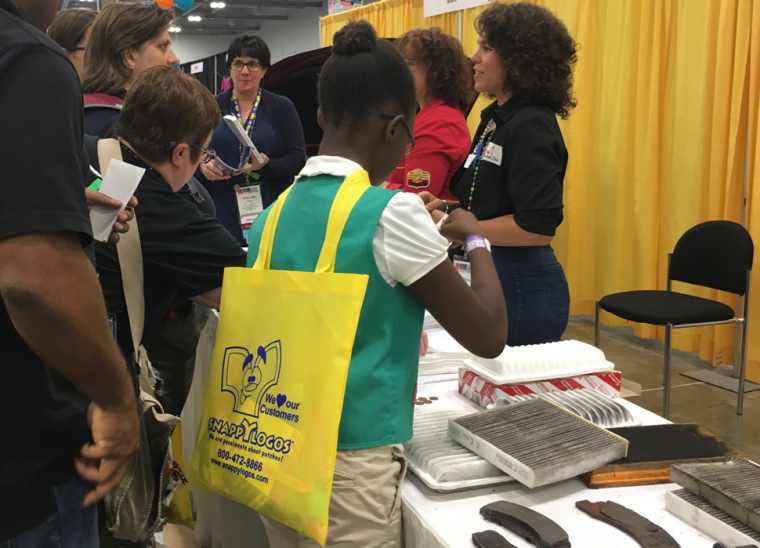 Patrice Banks showing girls around the engine of a car at G.I.R.L. 2017