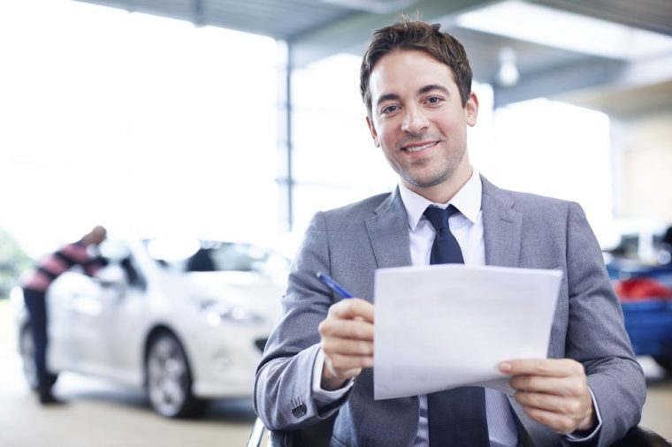 car salesman selling gap insurance paperwork