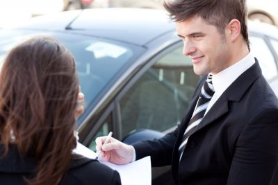 car salesman used car paperwork