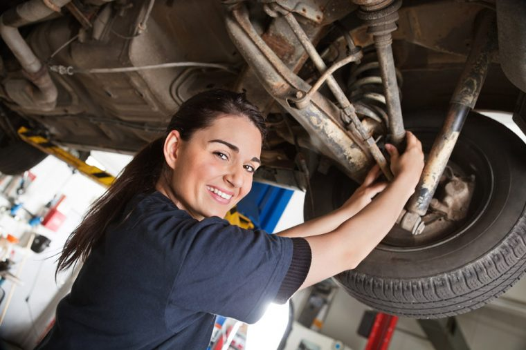 female mechanic woman car maintenance work garage axle differential vehicle parts drive wheel