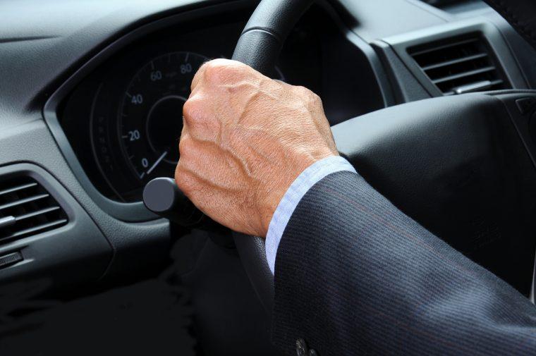 Hands tight on steering wheel