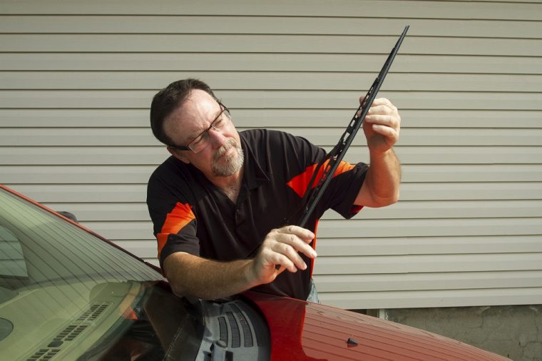 man changing windshield wipers inspection