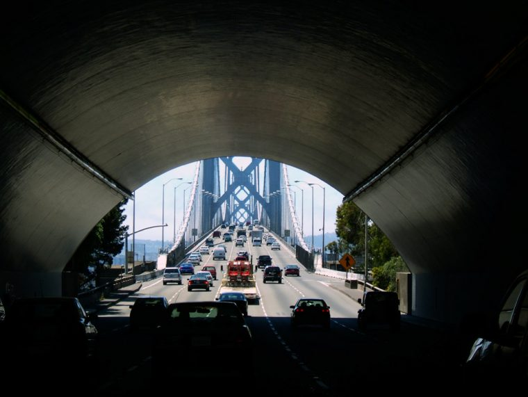 cars in a tunnel going to a bridge