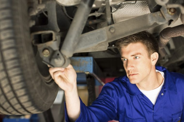 mechanic working on a car in body shop