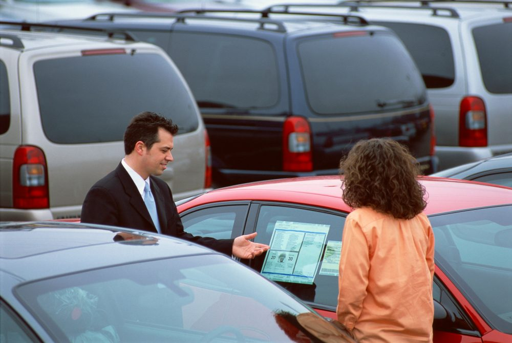 Woman looking at used cars on a lot with a male salesperson