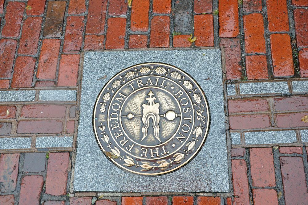 A marker from the Boston Freedom Trail, surrounded by red bricks