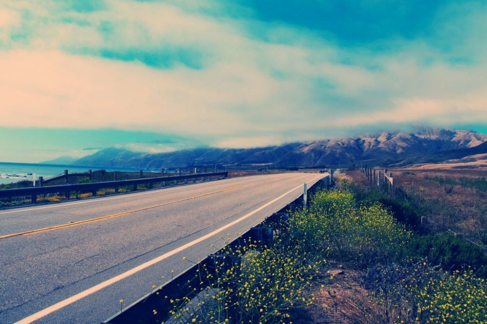 artistic view of the Pacific Coast Highway with mountains in the background and the ocean on the left
