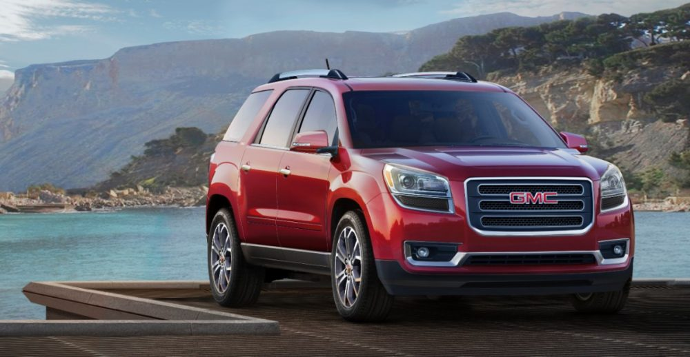 2013 GMC Acadia parked by a lake in a mountain range
