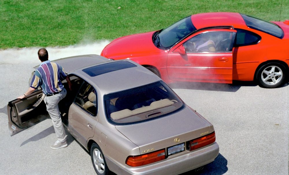 Man in a gold sedan getting out of his car after a collision with a woman in a red coupe