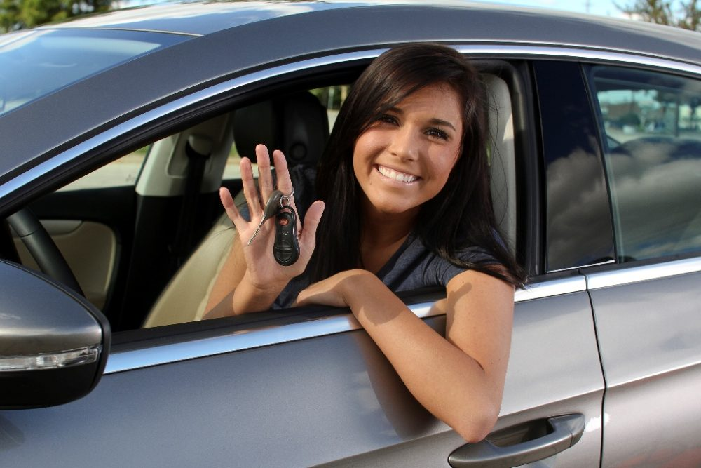 female driver  with long dark hair sitting in a gray sedan and holding a set of car keys