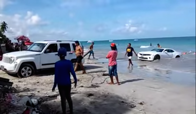 A Jeep Liberty attempts to pull a beached Camaro in this YouTube video