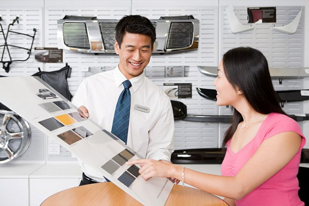 Asian woman at car dealership shopping browsing salesman lingo