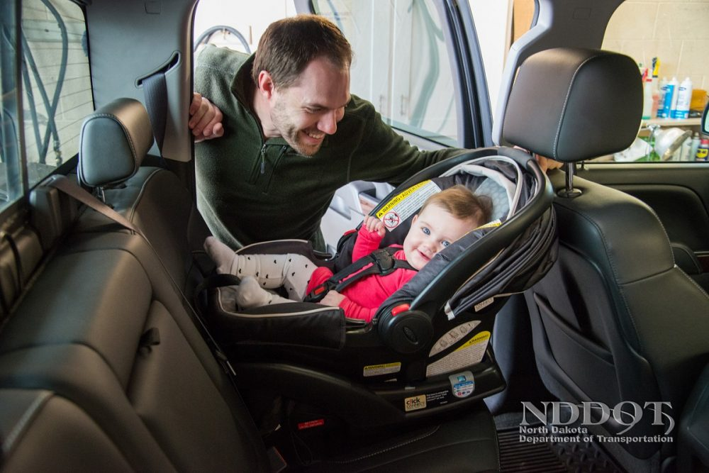 Man strapping child into rear-facing car seat