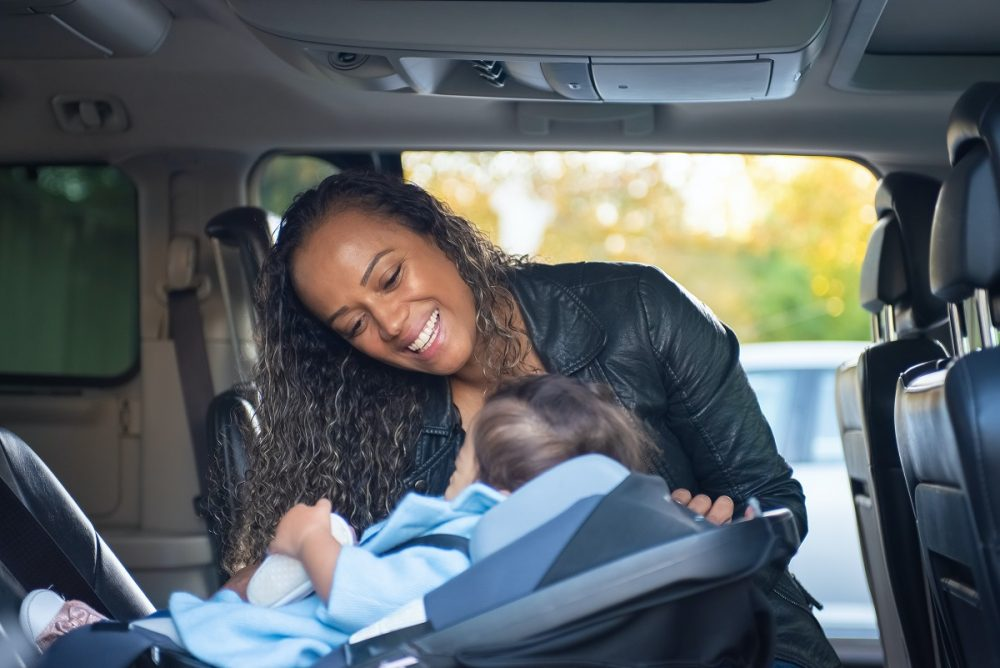 Woman strapping child into rear-facing car seat