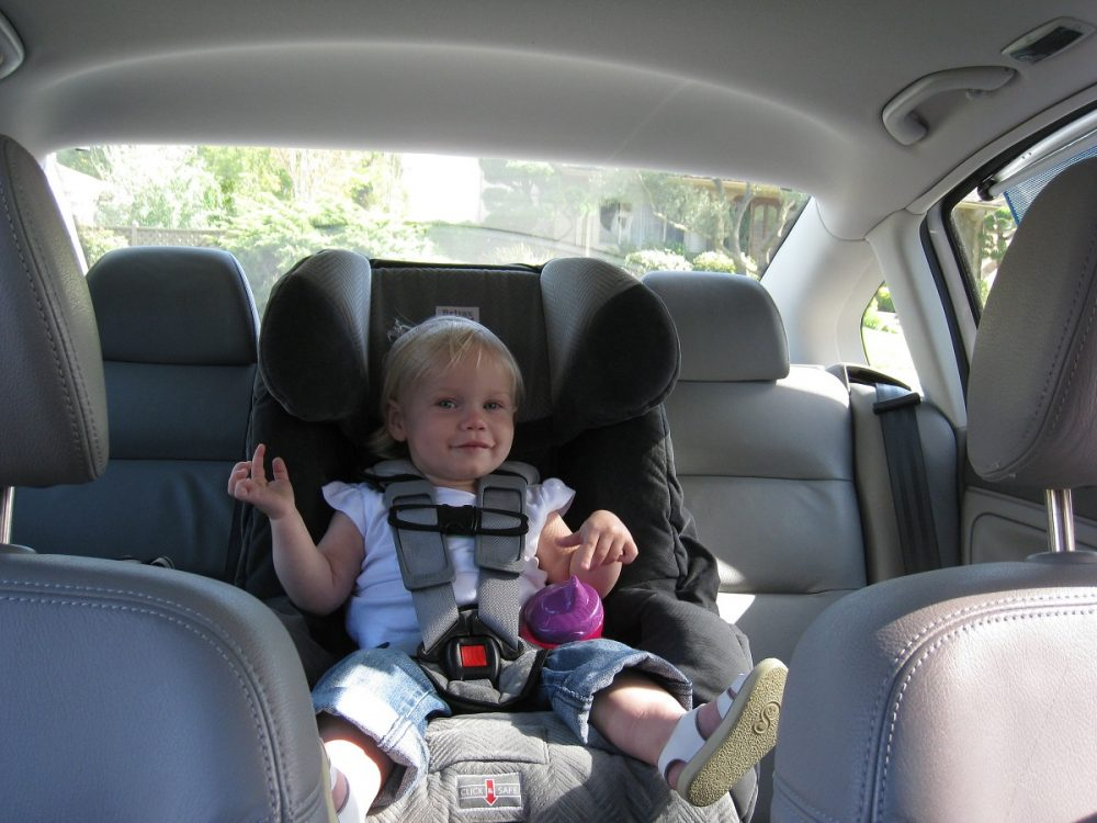 child in front-facing car seat secured in the rear middle seat