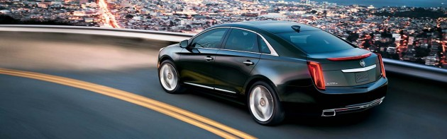 The 2015 Cadillac XTS features swooping lines across the sides and an upright front and rear end.