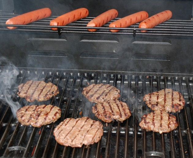 how to properly tailgate - grilling up burgers and hot dogs