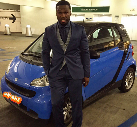 Rapper 50 Cent poses in front of Smart car.