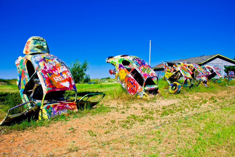 Painted Volkswagen Beetles sticking out of the ground at VW Slug Bug Ranch in Conway, Texas