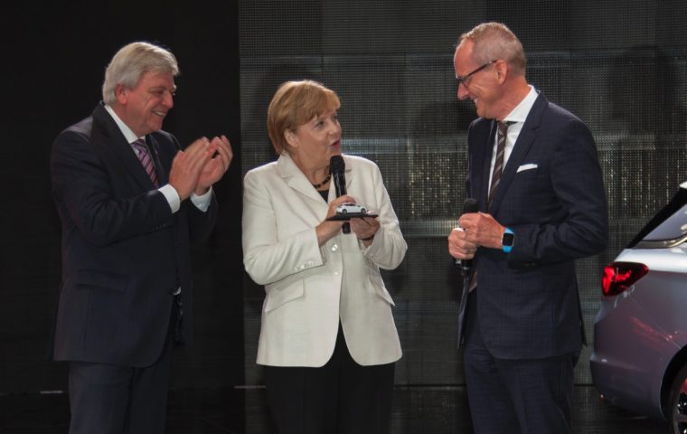 German Chancellor Angela Merkel is presented with a model of an Opel Astra at IAA