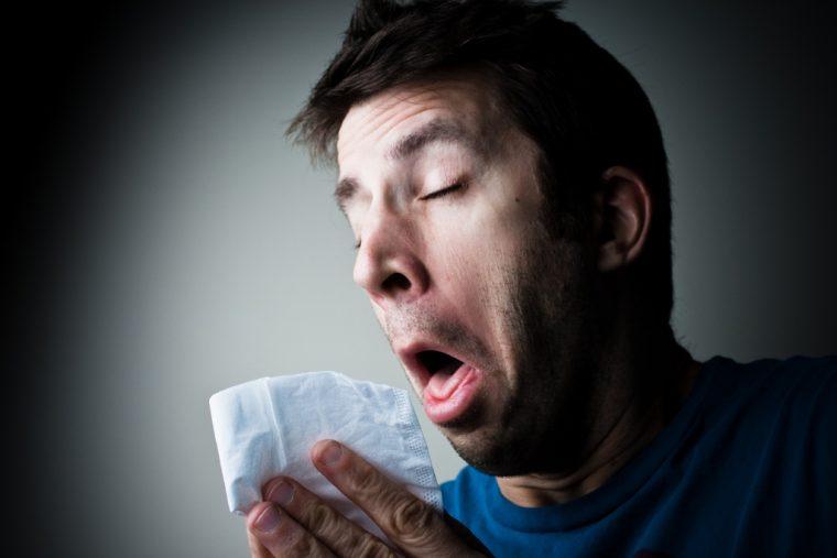 man sneezing cold tissue