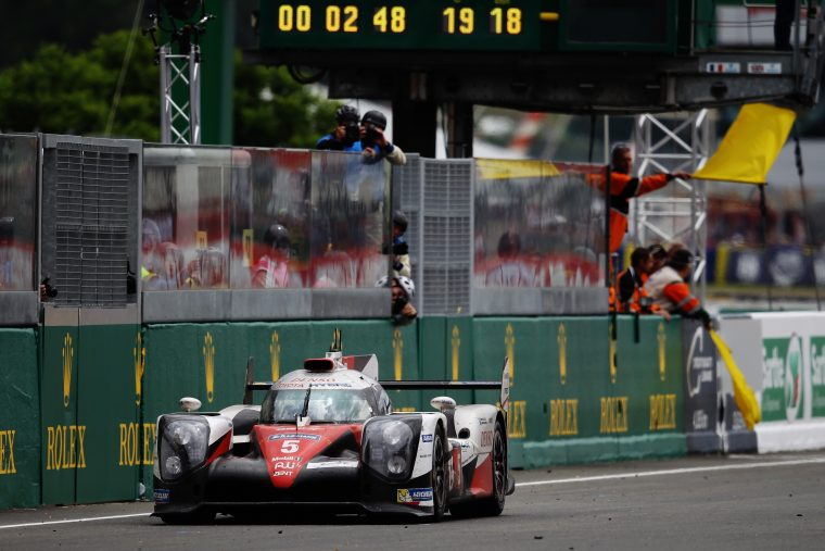 The Toyota #5 TS050 Hybrid at a stop near the pit wall.