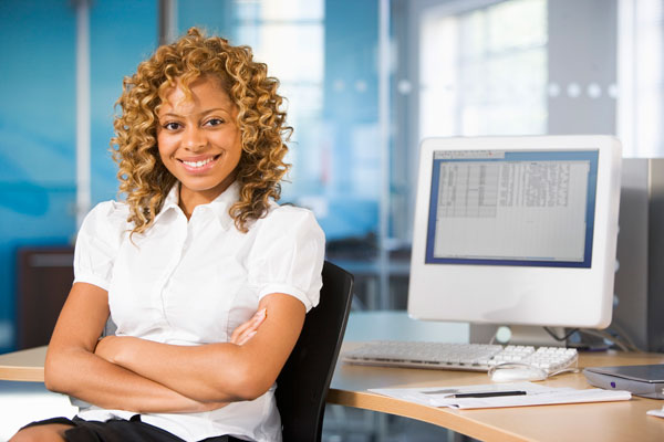 Young woman by computer desk working