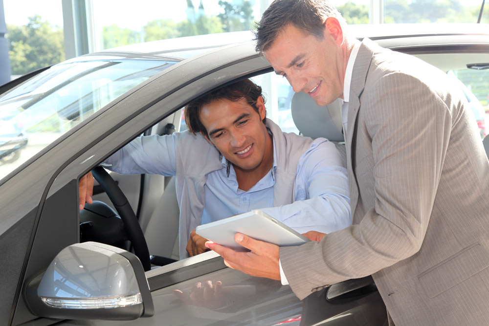 car dealership salesperson standing outside a car and customer sitting inside a car, look at a tablet together