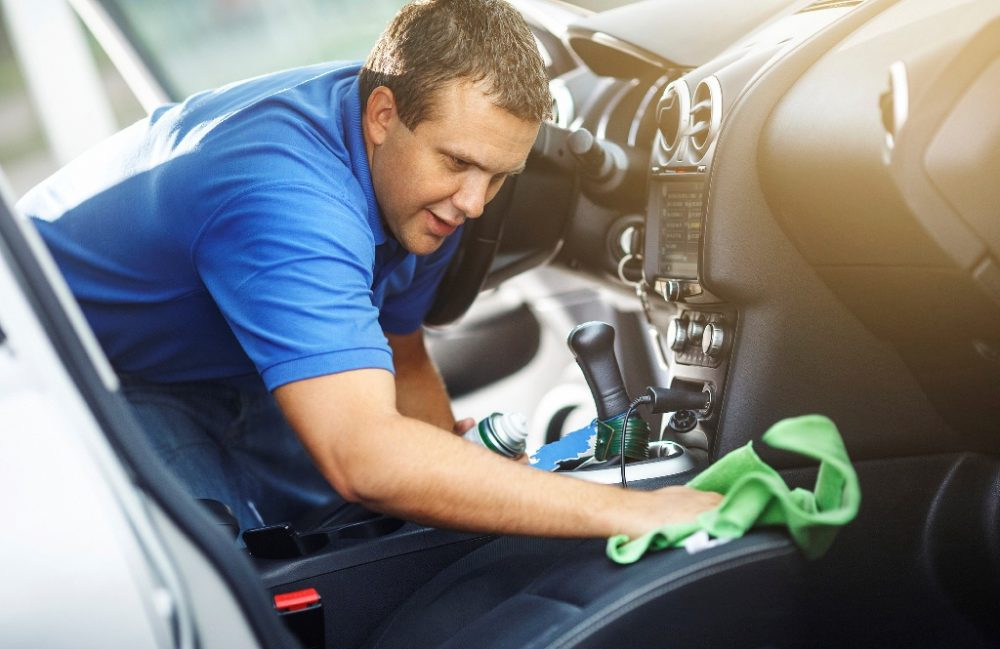 man cleaning car interior and wiping leather seats